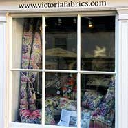 A display of Voyage fabrics and cushion covers in the window of our new workshop.